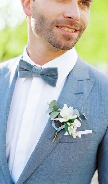 ดอกไม้สขาวเเมตท์เข้ากับชุดสูทสีฟ้าทำให้ชุดดูเด่นขึ้น